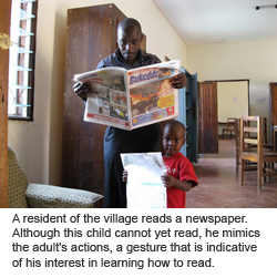 A resident of the village reads a newspaper. Although this child cannot yet read, he mimics the adult's actions, a gesture that is indicative of his interest in learning how to read.
