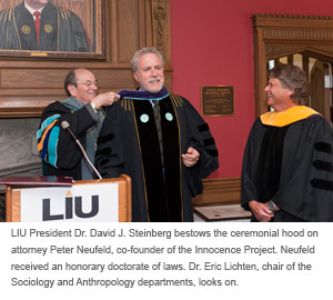 ) LIU President Dr. David J. Steinberg bestows the ceremonial hood on attorney Peter Neufeld, co-founder of the Innocence Project. Neufeld received an honorary doctorate of laws. Dr. Eric Lichten, chair of the Sociology and Anthropology departments, looks on.