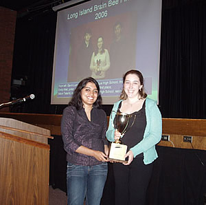 Saroj Kunnekatt (left) presenting the 2006 Long Island University Brain Bee first place trophy to champion Emily Weil at the annual Research Symposium held at Lynbrook High School. Saroj and Emily both attended the Brain Bee workshops held at Long Island University. Dr. David Shenker facilitated the Lynbrook High School participation.