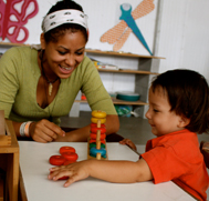 teacher with young child playing with blocks at desk