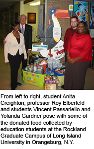 From left to right, student Anita Creighton, professor Roy Elberfeld and students Vincent Passariello and Yolanda Gardner pose with some of the donated food collected by education students at the Rockland Graduate Campus of Long Island University in Orangeburg, N.Y.